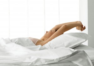 Young woman in bed, stretching arms over head